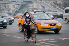 Bike in Beijing. Beijing, China - March 31th, 2013: Woman with protective mask riding bike on a busy street in Dongcheng District Royalty Free Stock Photo