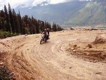 Bike and biker. Negotiating a sharp turn while climbing to Rohtang pass near Manali, India Royalty Free Stock Photo