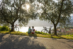 Bike break by sunrise on garda lake (italy). Woman and men enjoy the garda lake view Royalty Free Stock Photography