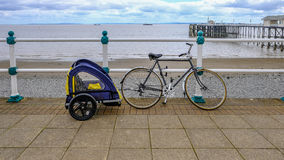 Bike with child cycle trailer, secured to railing on the sea fro. Bike with child cycle buggie, secured to railing on the sea front. Shows beach and sea and pier stock photo