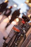 Bike in the city, dusk: Rear picture of a city bike, blurred background. Rear picture of a city bike, blurry background with city lights, evening, bicycle stock photos