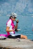 Bike coffee break at garda lake. Girl drinks a coffee on the lake Stock Images