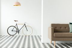 Bike contra uma parede vazia, um sofá colhido e um assoalho quadriculado dentro foto de stock royalty free
