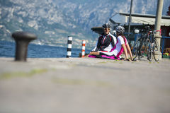 Bike conversation at the lake. A couple after cyclingtour to discuss Stock Image