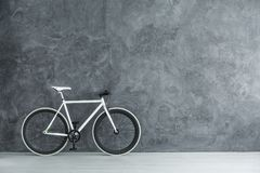 Bike with copy space. Photo with copy space of white bike standing in a room with raw grey wall Stock Photo