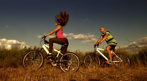 Bike couple хъ. Sport couple riding bikes in field Royalty Free Stock Photography