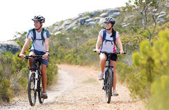 Bike couple. Happy carefree mountain bike couple cycling outdoors and leading a healthy lifestyle Royalty Free Stock Photos