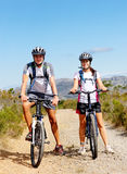 Bike couple. Happy carefree mountain bike couple cycling outdoors and leading a healthy lifestyle Royalty Free Stock Photo