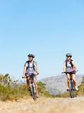 Bike couple. Happy carefree mountain bike couple cycling outdoors and leading a healthy lifestyle Royalty Free Stock Image