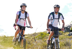 Bike couple. Happy carefree mountain bike couple cycling outdoors and leading a healthy lifestyle Royalty Free Stock Images