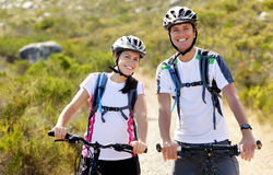 Bike couple. Happy carefree mountain bike couple cycling outdoors and leading a healthy lifestyle Stock Image