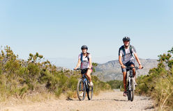 Bike couple. Happy carefree mountain bike couple cycling outdoors and leading a healthy lifestyle Royalty Free Stock Photography