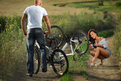 Bike couple. Bicycle has flat tyre and men helps his girlfriend pump it up Royalty Free Stock Photography