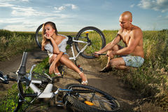 Bike couple. Bicycle has flat tyre and men helps his girlfriend pump it up Stock Photo
