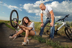 Bike couple. Bicycle has flat tyre and women pumping it up Royalty Free Stock Photography