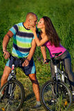Bike couple. Lovely couple riding bikes in field Stock Images