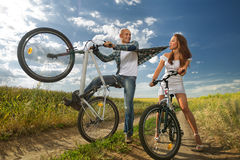 Bike couple. Couple riding bikes in field Stock Images