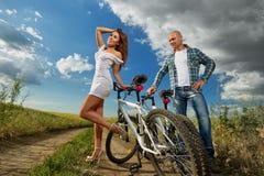 Bike couple. Romantic young bike couple on field Royalty Free Stock Image