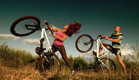 Bike couple. Sport couple riding bikes in field Royalty Free Stock Images