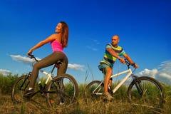 Bike couple. Sport couple riding bikes in field Stock Photo