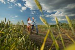Bike couple. Walking on field Royalty Free Stock Photo