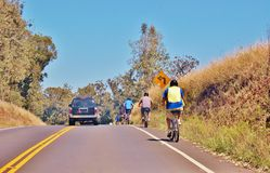 Bike down in Haleakala volcano area. Bicycle tour  is staged outside the entrance to the park at an elevation of about 6500 feet. Tour instructors picking you up Royalty Free Stock Photo