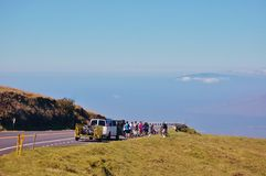 Bike down in Haleakala volcano area. Bicycle tour  is staged outside the entrance to the park at an elevation of about 6500 feet. Tour instructors picking you up Royalty Free Stock Images