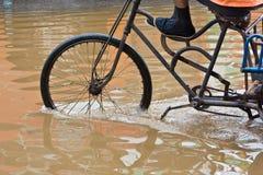 Bike el montar a caballo a través de las calles inundadas Imagen de archivo libre de regalías