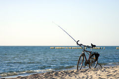 Bike and fishing rod. A bike and a long fishing rod standing on a beach Royalty Free Stock Image