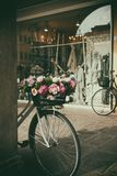 Bike with flowers in the basket lying next to the wall. royalty free stock photos