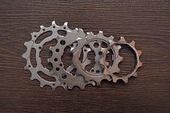 Bike gears. Four bicycle gears on wood Stock Image