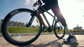 A bike is getting driven away by an athlete with a bionic leg. 4K stock footage
