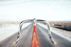 Bike handlebar, travel concept. Close up of red bike handlebar on road backgrpound. Travel concept. 3D Rendering Royalty Free Stock Photos