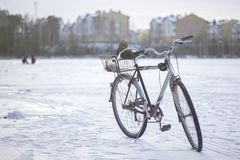Bike on ice on winter fishing. Bike on winter fishing in the background of apartment buildings and two fishermen, toned Stock Photo
