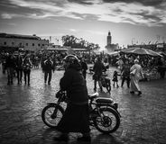 Bike on Jemaa El-Fna square. In Marrakesh a man is walking on Jemaa El-Fna square with his bike. Picture taken in 2017 in black and white Stock Image