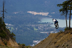 Bike Jump over valley. A mountain biker jumps with a mountain valley vista in the background Royalty Free Stock Photo