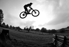Bike jump silhouette. Silhouette of a young man performing a radical mountain bike jump Stock Photos