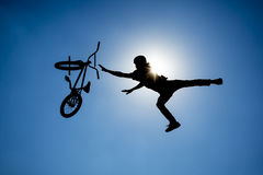Bike jump silhouette. An extreme rider is making a free style jump from a ramp. The young boy with his bicycle is seen as a silhouette in front of the sun Stock Photography
