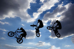 Bike jump silhouettes multiple exposure. An extreme rider is making a free style jump from a ramp. The young boy with his bicycle is seen as a silhouette in Stock Photo