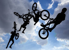 Bike jump silhouettes multiple exposure. An extreme rider is making a free style jump from a ramp. The young boy with his bicycle is seen as a silhouette in Stock Images