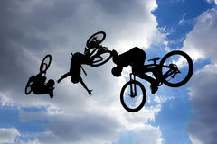 Bike jump silhouettes multiple exposure. An extreme rider is making a free style jump from a ramp. The young boy with his bicycle is seen as a silhouette in Royalty Free Stock Image