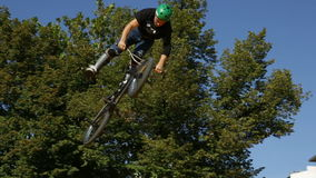 Bike jump trees. Sofia, Bulgaria - September 24, 2016: An extreme rider is making a free style jump from a ramp. The young boy with his bicycle is seen up in the stock video footage