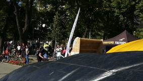 Bike jump trees. Sofia, Bulgaria - September 24, 2016: An extreme rider is making a free style jump from a ramp. The young boy with his bicycle is seen up in the stock footage