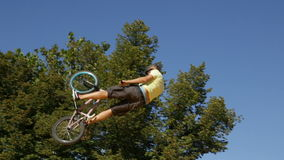 Bike jump trees. Sofia, Bulgaria - September 24, 2016: An extreme rider is making a free style jump from a ramp. The young boy with his bicycle is seen up in the stock video