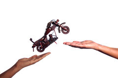 Bike Jumping from one hand to other. A wooden bike jumping from one hand to other hand , Isolated in white background Stock Photos