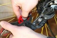 Bike la riparazione, cambiamento delle mani il dettaglio sulla ruota Immagine Stock