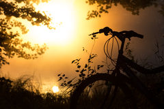 Bike on the lake in front of the setting sun Stock Image