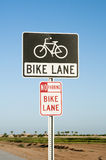 Bike Lane. Signs indicate the presence of a traffic lane reserved for bikers along a city street Stock Photography