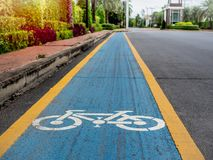 Bike lane. White bicycle icon on blue and yellow background on the old road in the village royalty free stock image