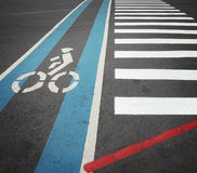 Bike lane in blue with biker symbol along with crosswalk Stock Images
